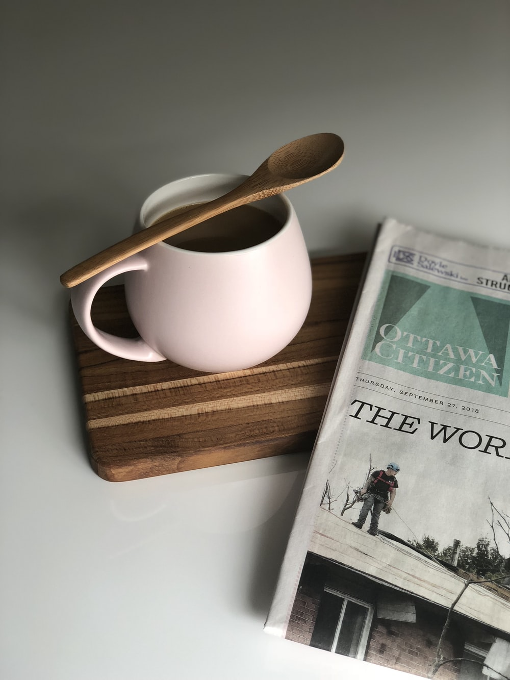 filled white ceramic mug and newspaper on white surface