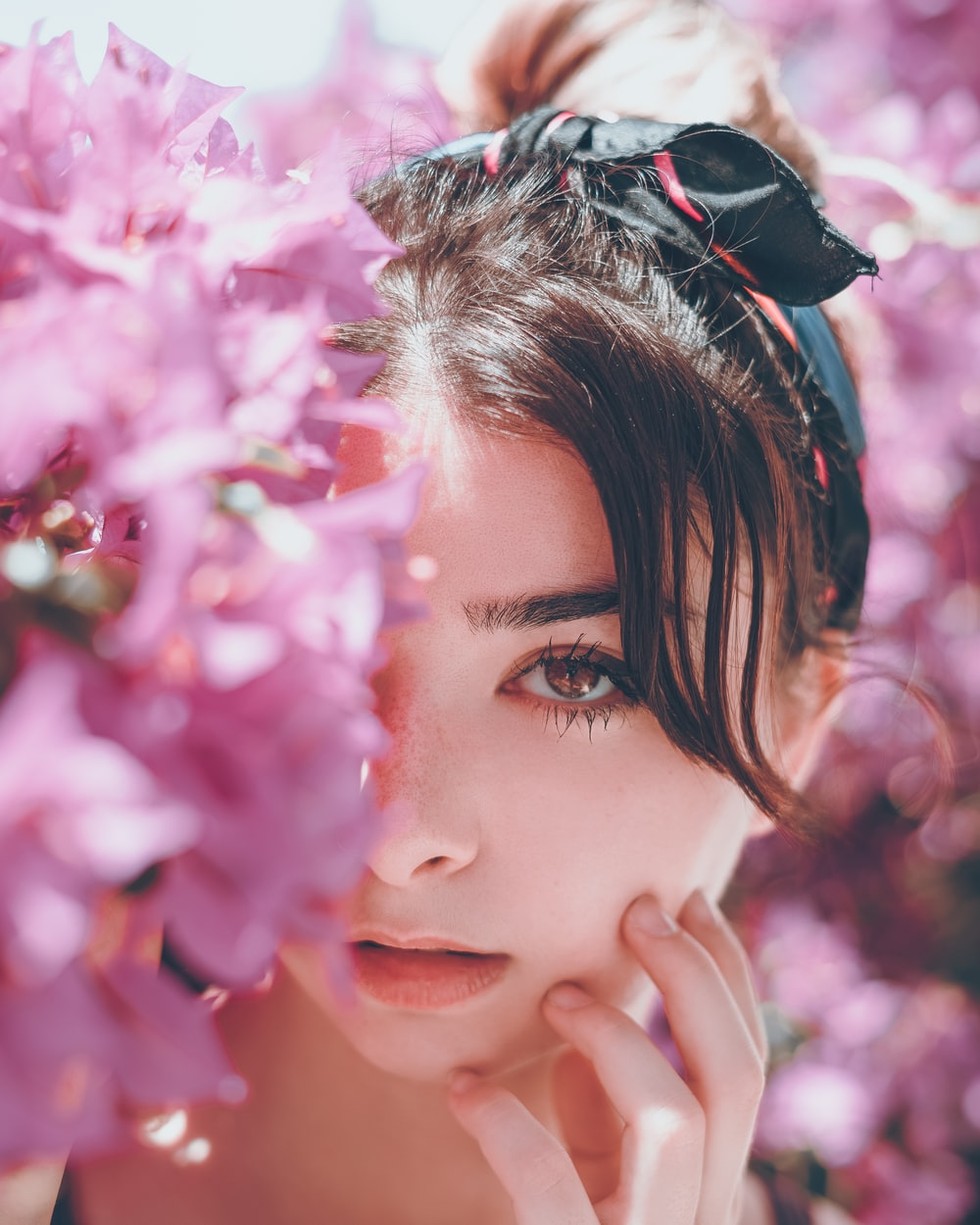 woman hiding on pink petaled flowers