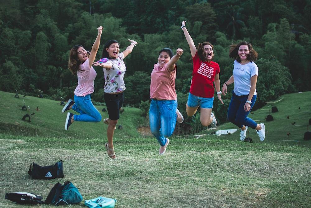 five women jumping on green grass