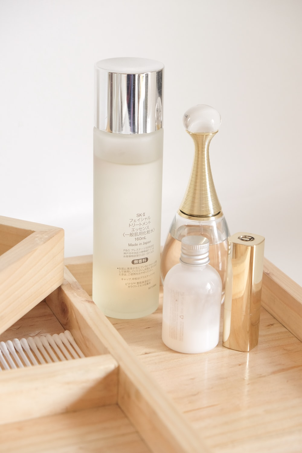 white and silver bottle on brown wooden rack
