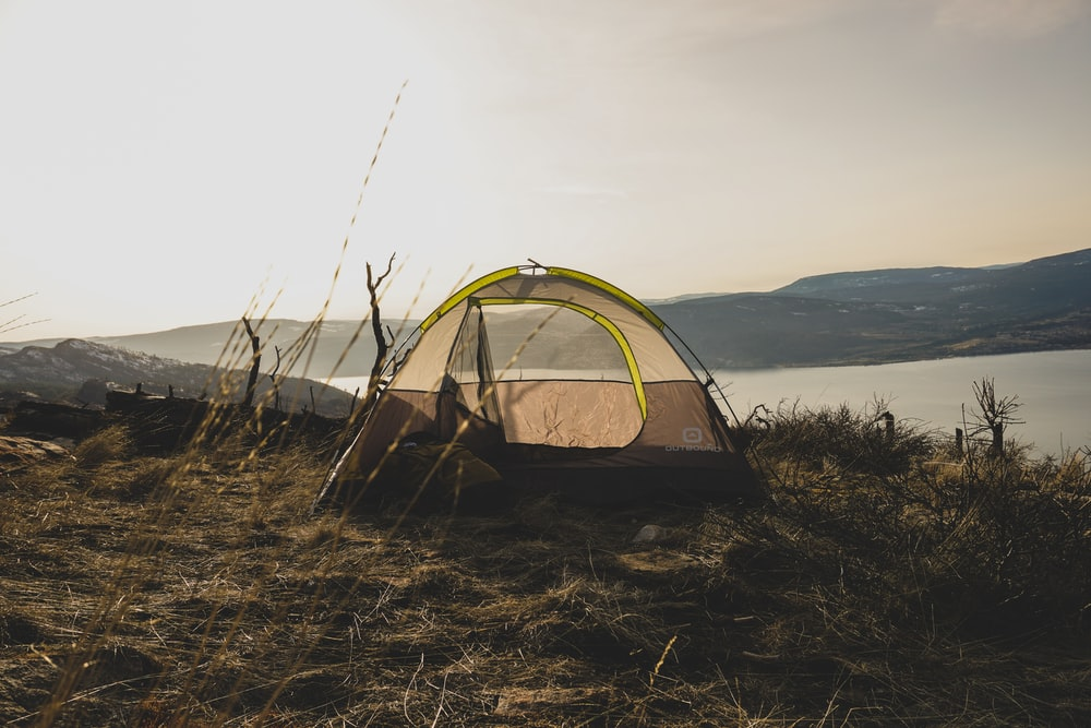 brown and gray tent near body of water during daytime