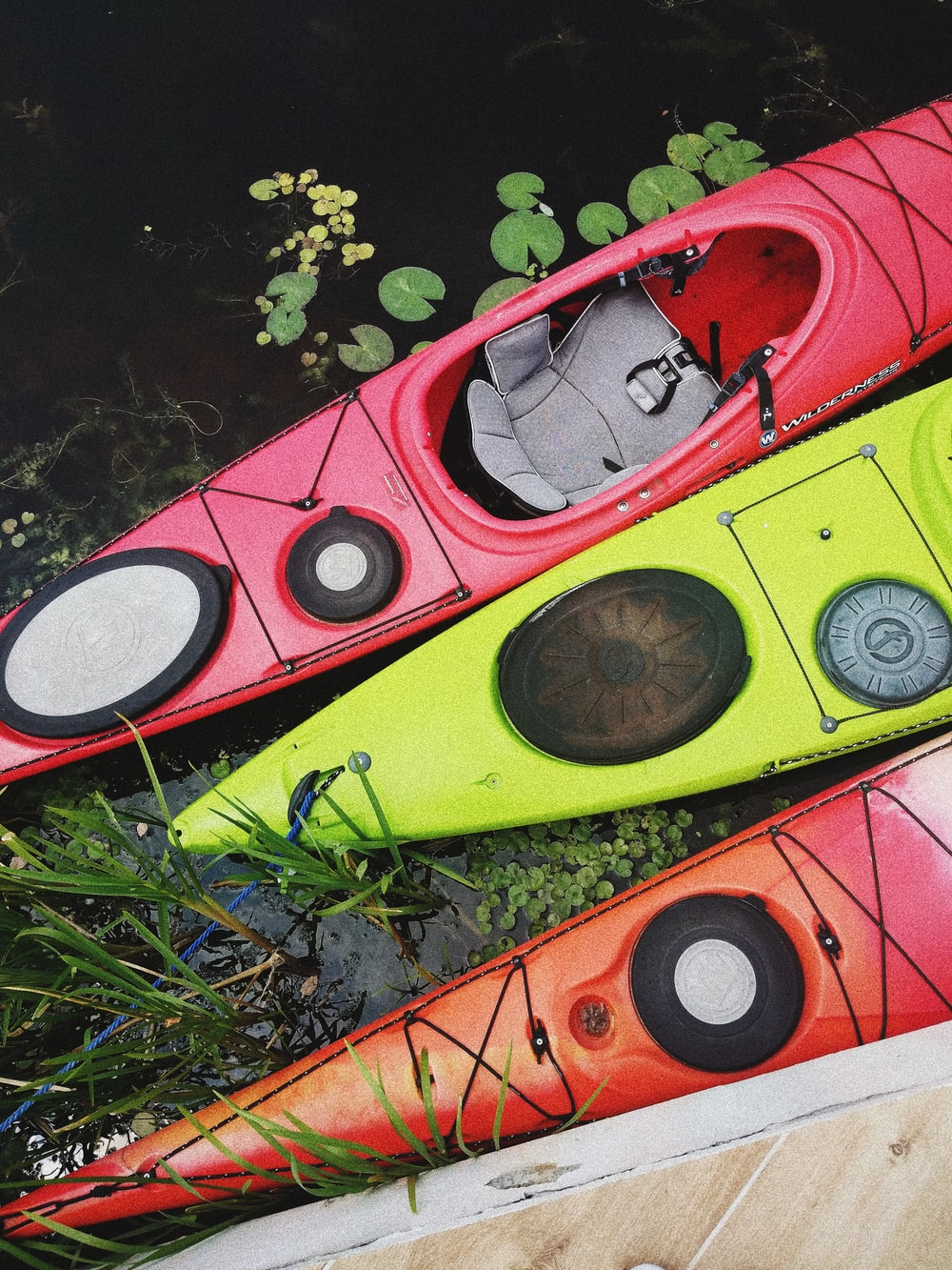 two red and one yellow kayaks on body of water
