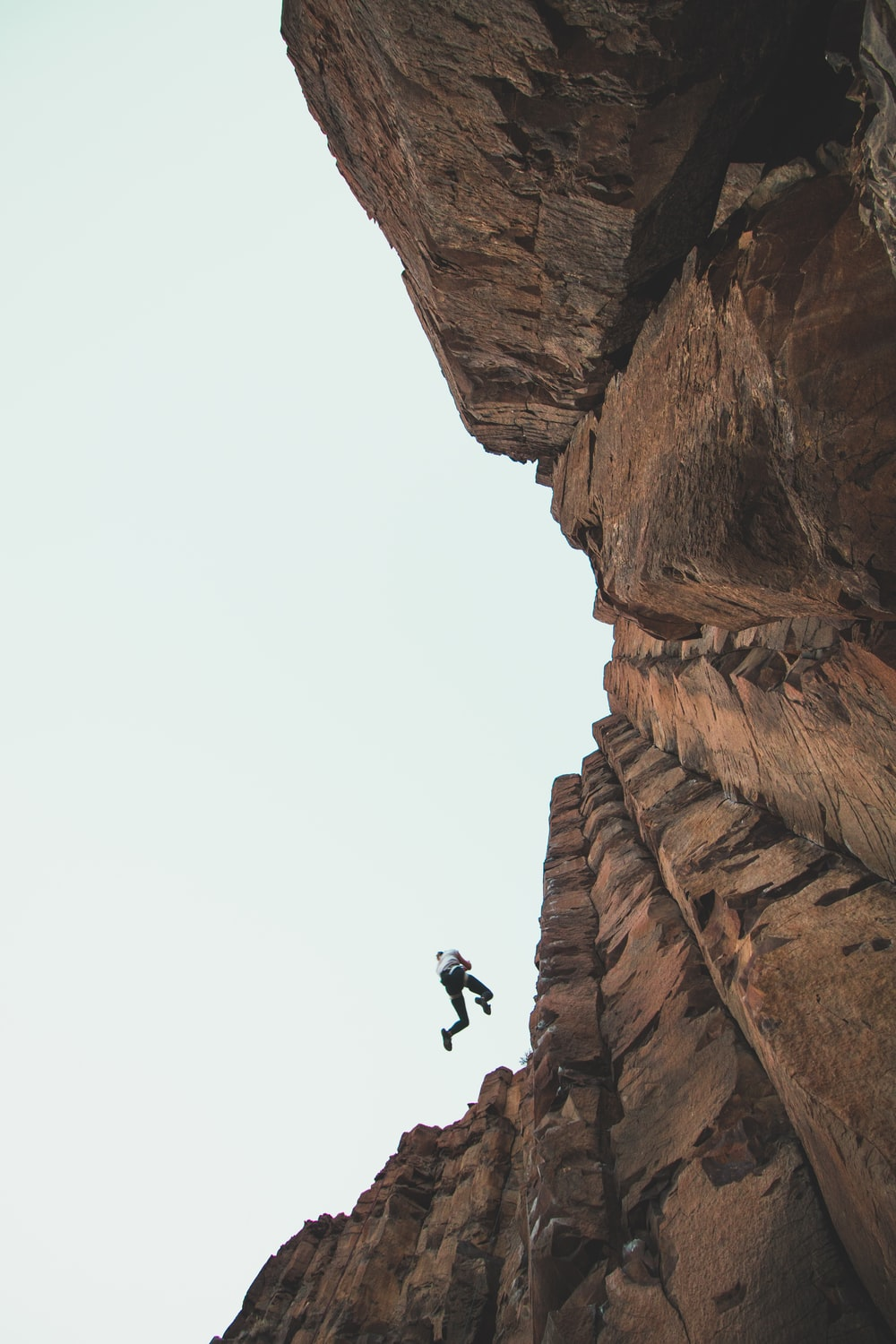 person climbing mountain during daytime