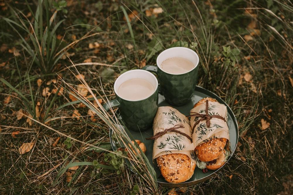 two hamburgers beside two ceramic mugs on tray