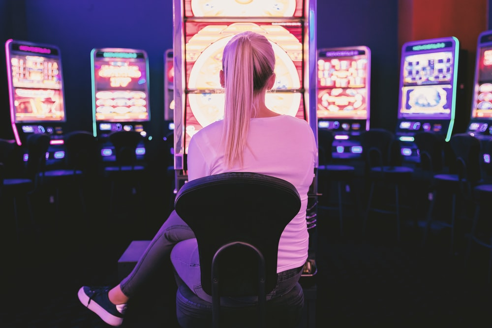 woman sitting facing arcade machine