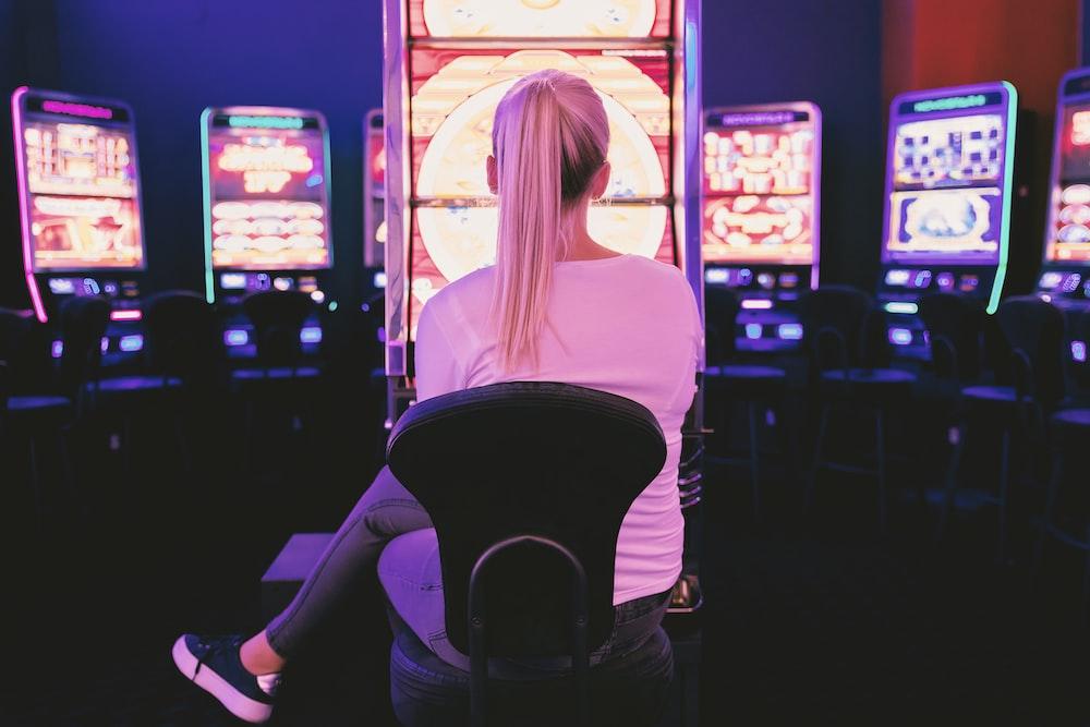 woman sitting facing arcade machine