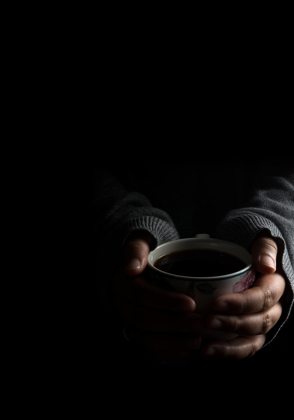 person in grey sweater holding cup with both hands