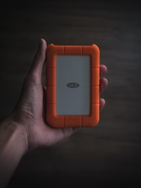 person holding white and orange Lace case