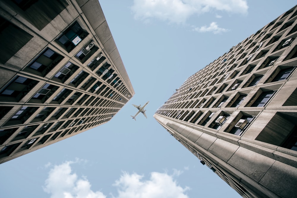 low angle photography of airplane crossing on two high rise buildings during daytime