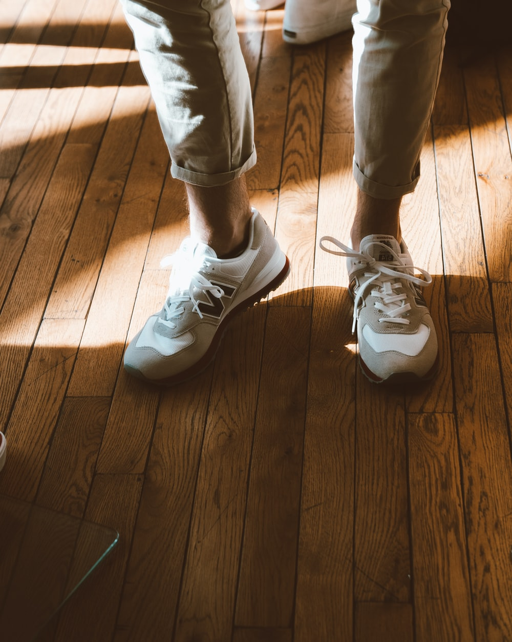 person wearing white New Balance shoes