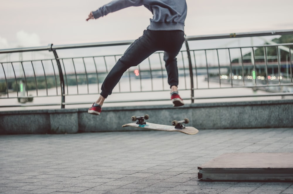 selective focus photography of person about to flip above using skateboard near railway and body of water