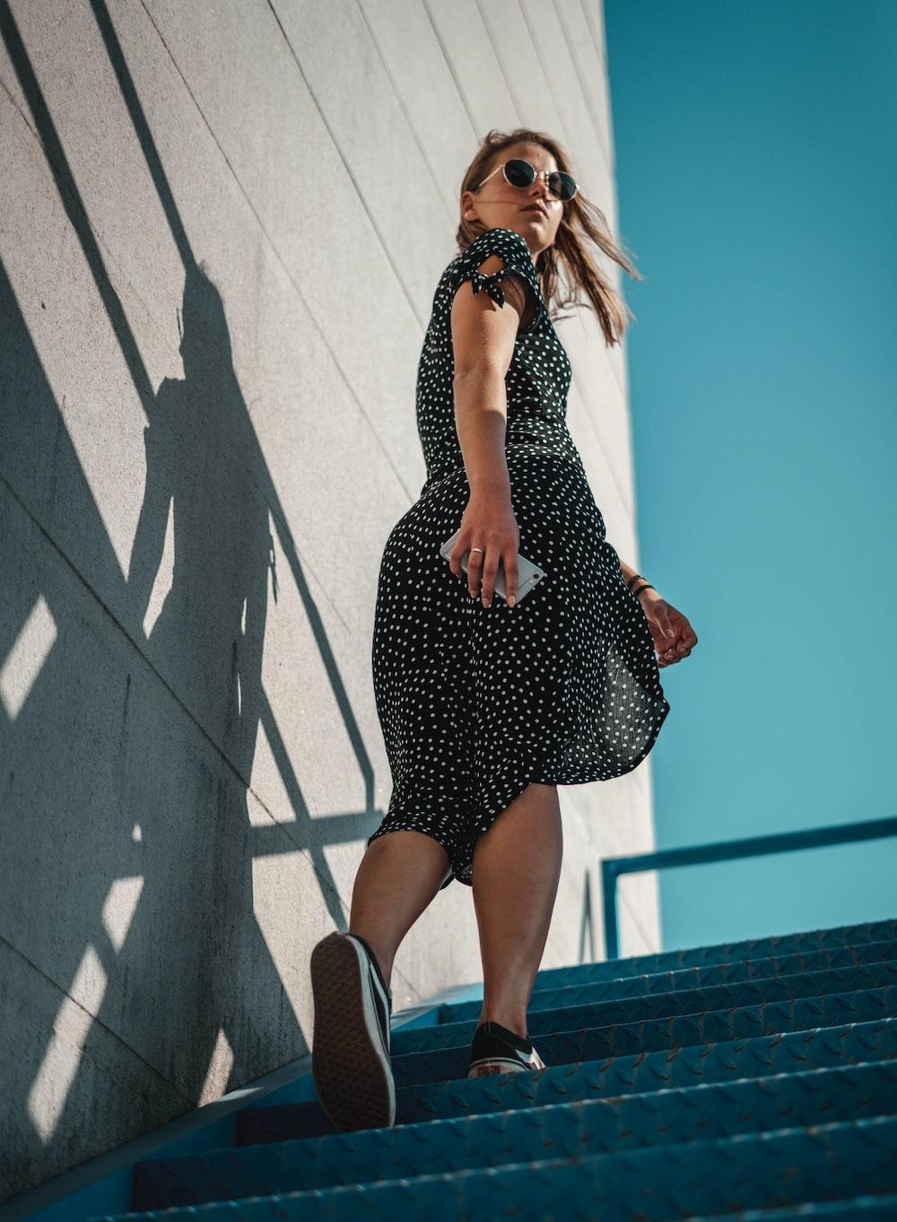 woman holding smartphone wearing black dress