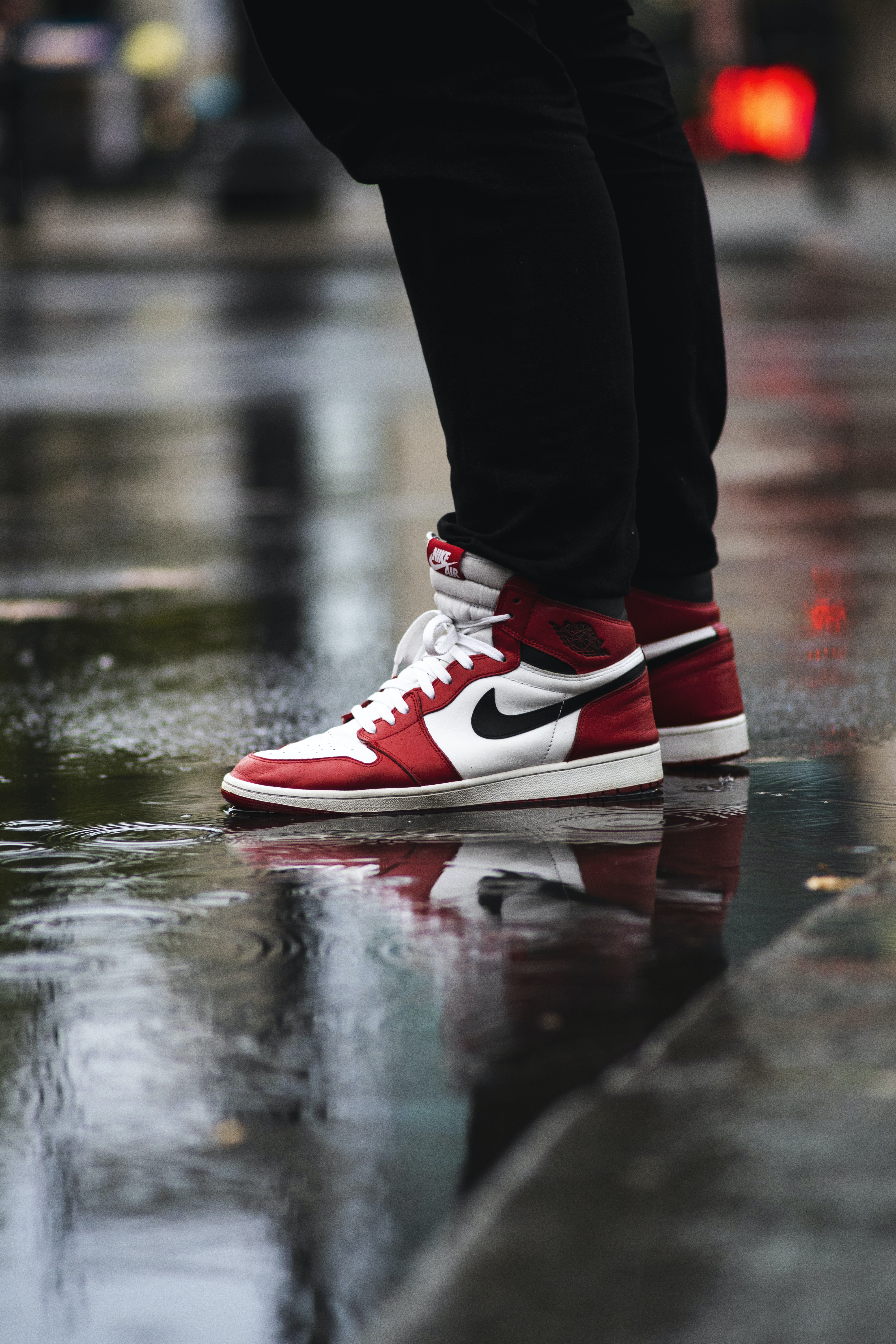 selective focus photography of person wearing white-red-and-black Air Jordan 1's Chicago