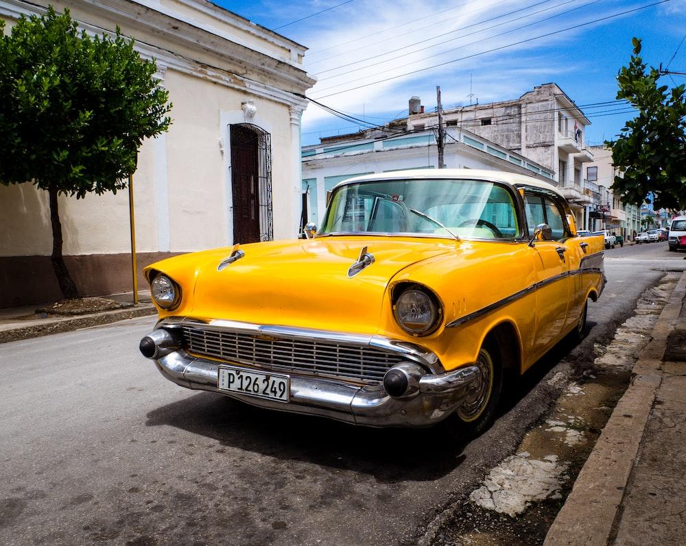 orange classic vehicle park on road