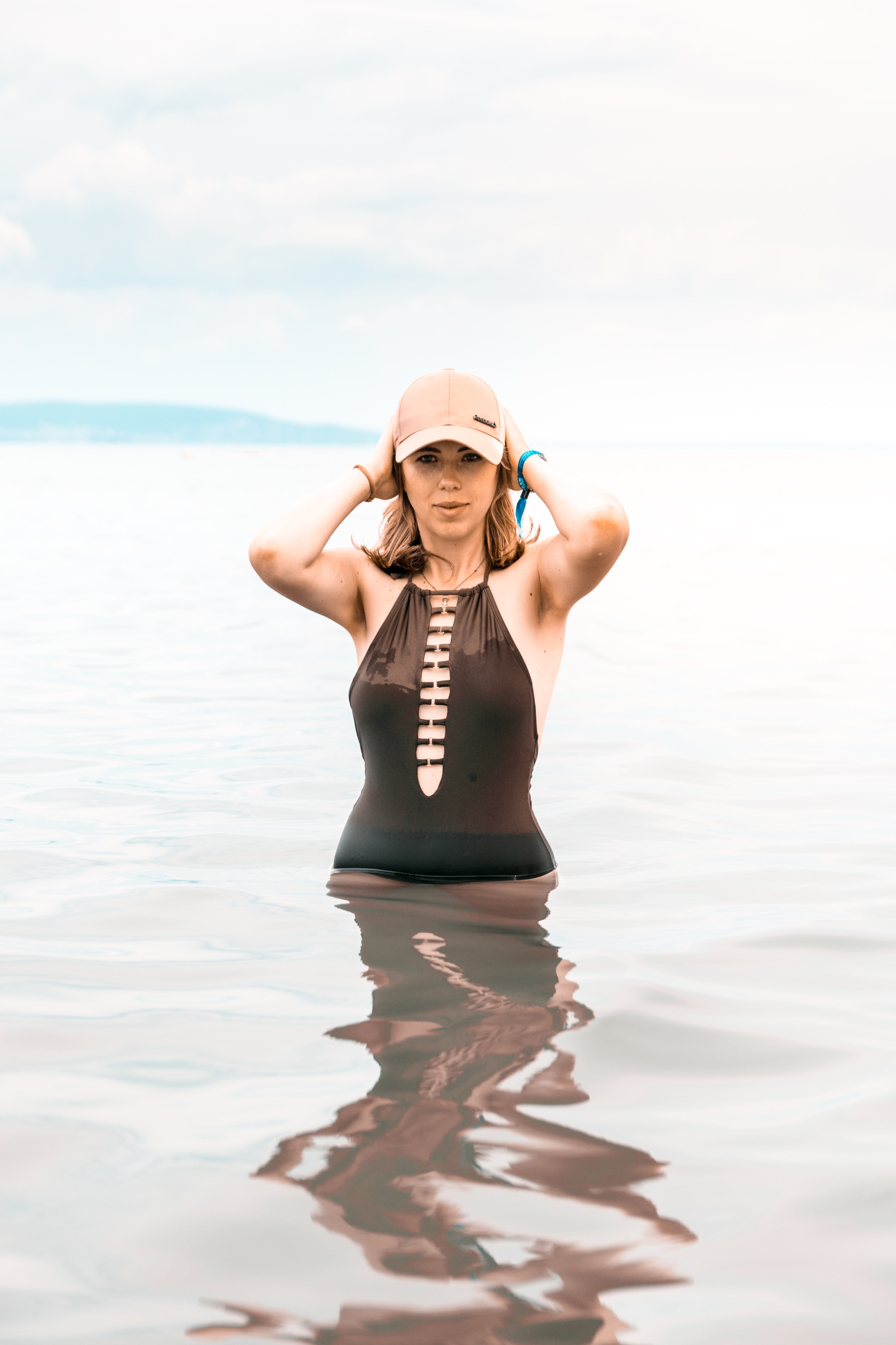woman wearing swimsuit and holding her cap