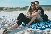 woman and man sitting on sand while hugging