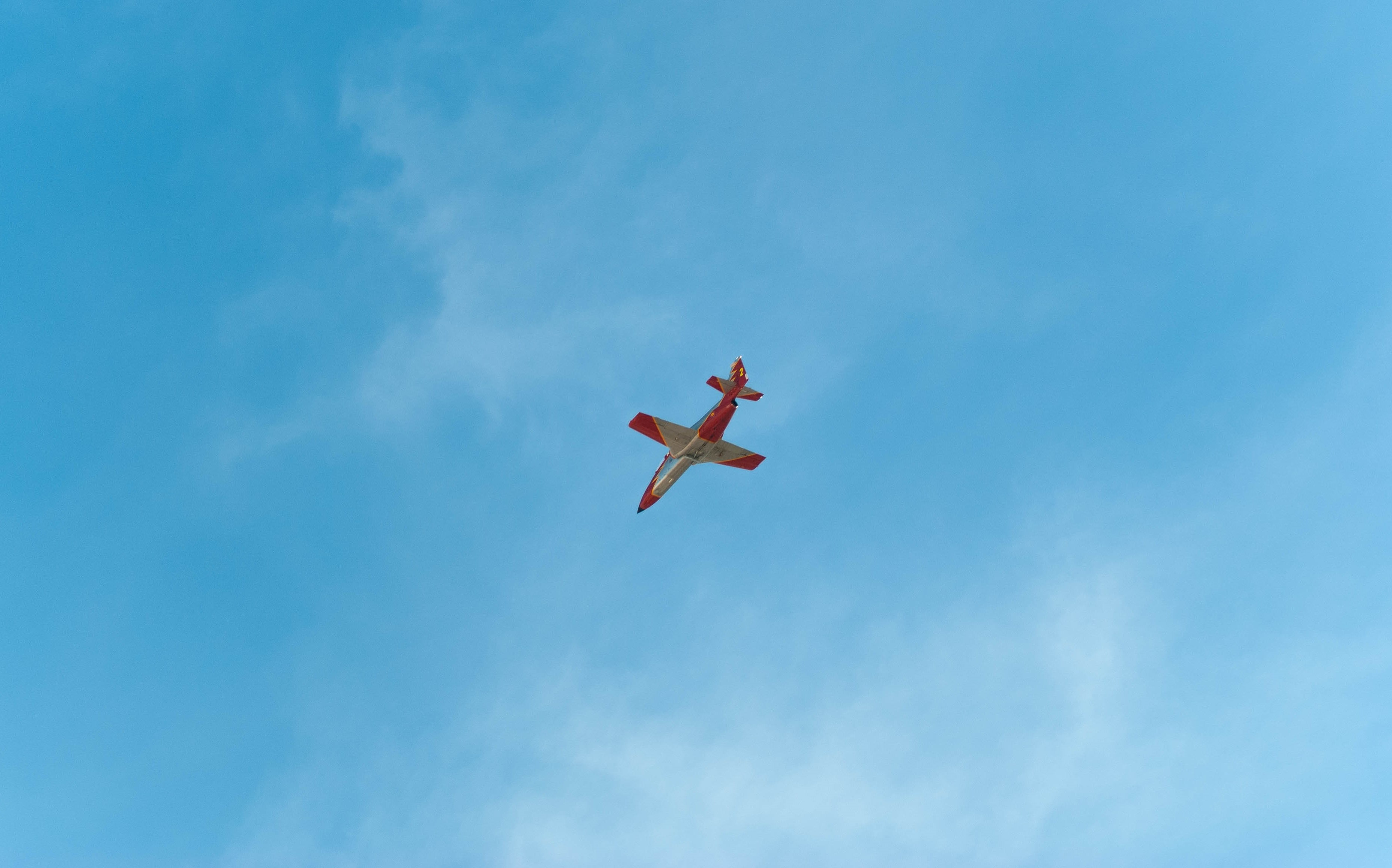 red and gray airplane on mid air during daytime