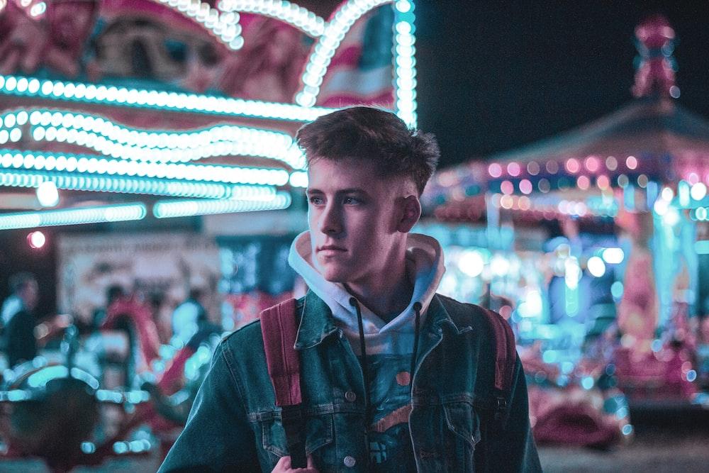 bokeh photography of man standing inside amusement park