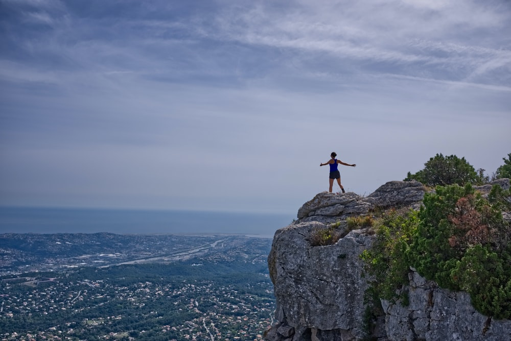 woman standing on cliff overlooking city during daytime