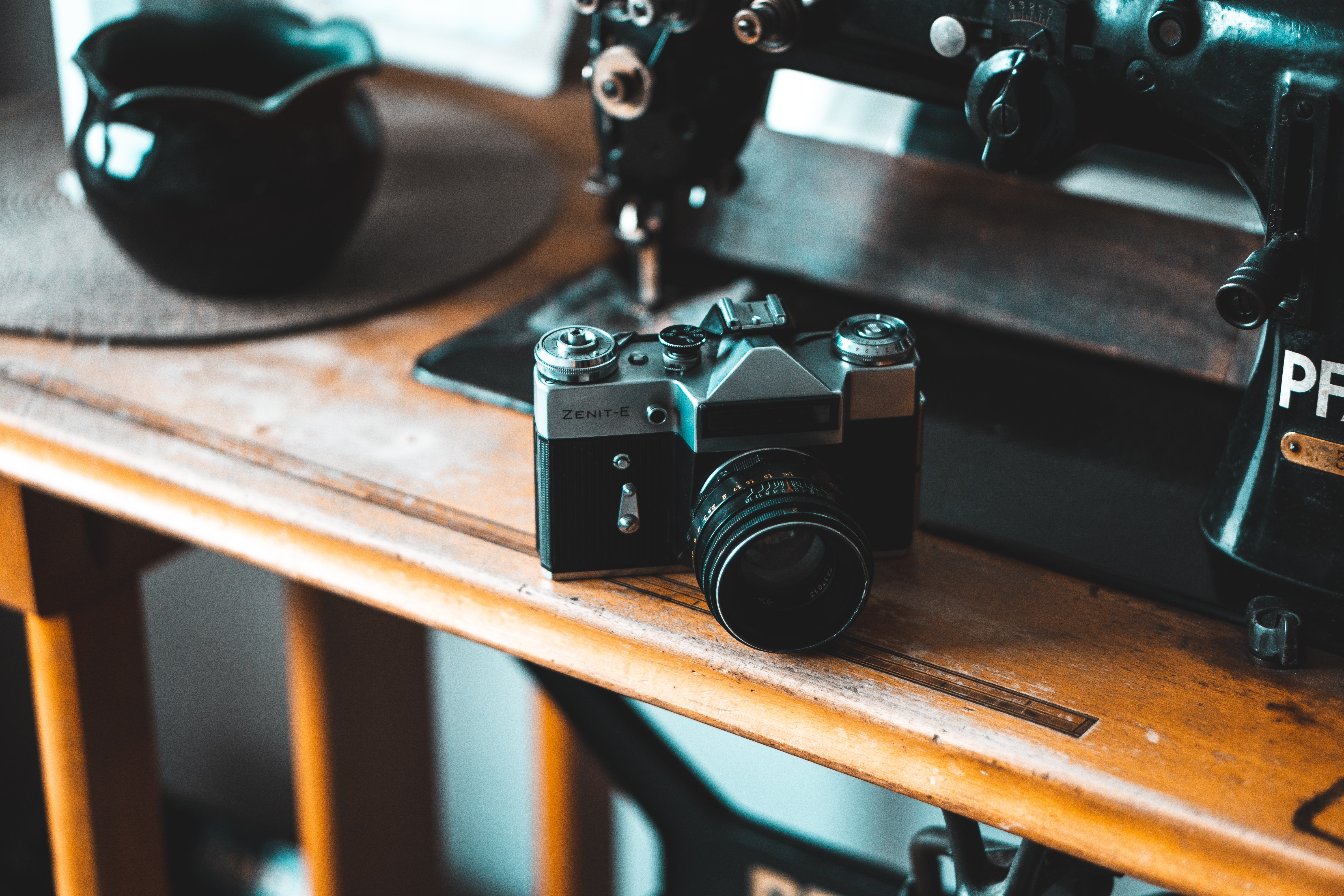 black and gray SLR camera beside sewing machine