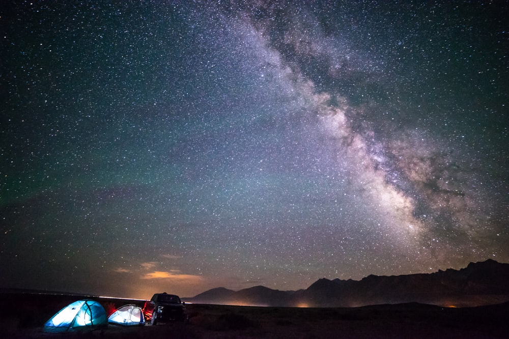 two blue tents under night skies with milky way