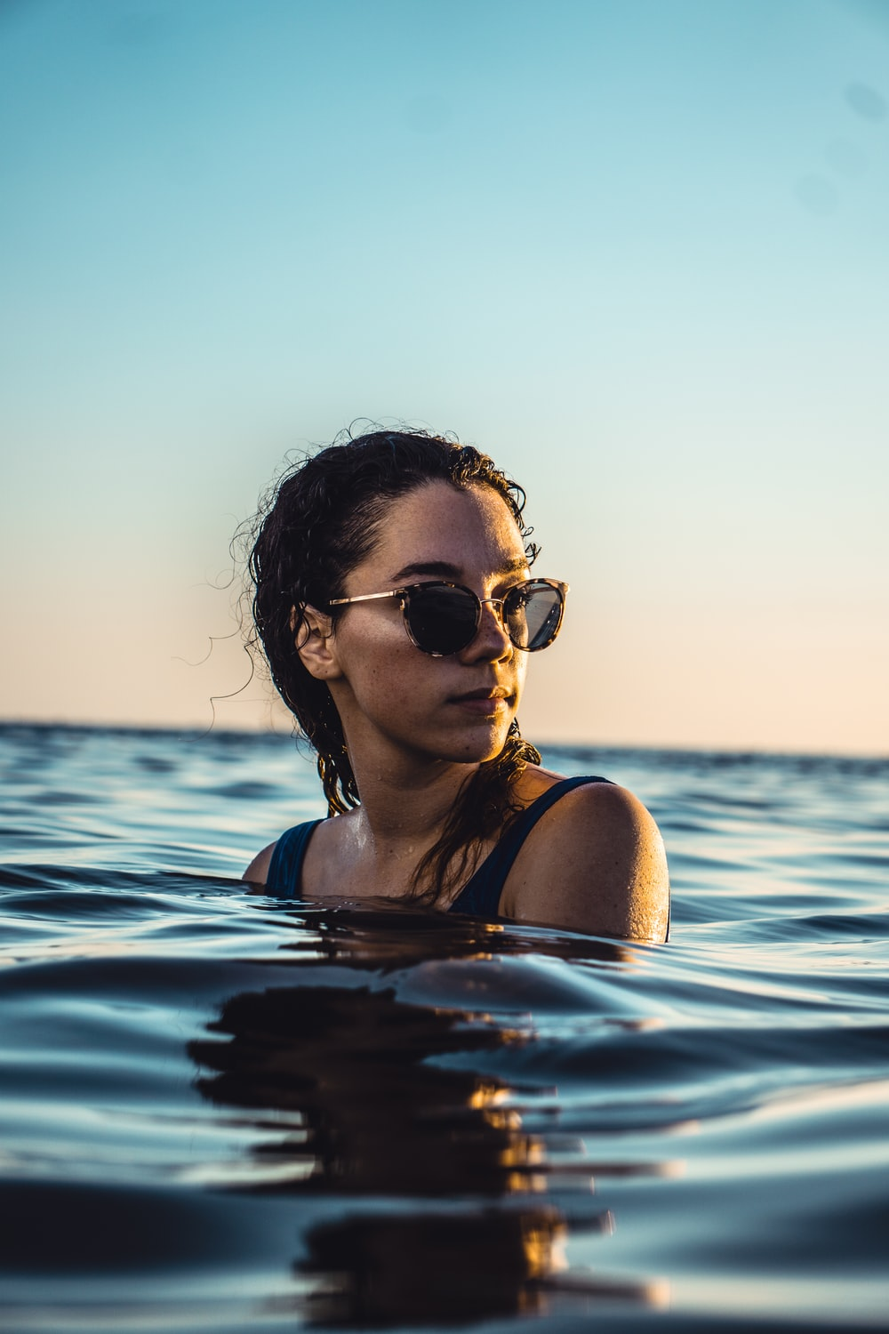 woman standing in body of water during daytime