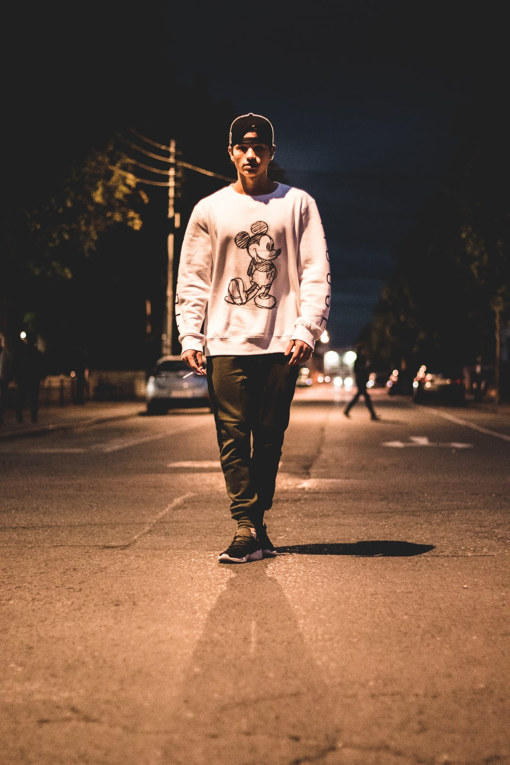 man standing in the middle of road during nighttime