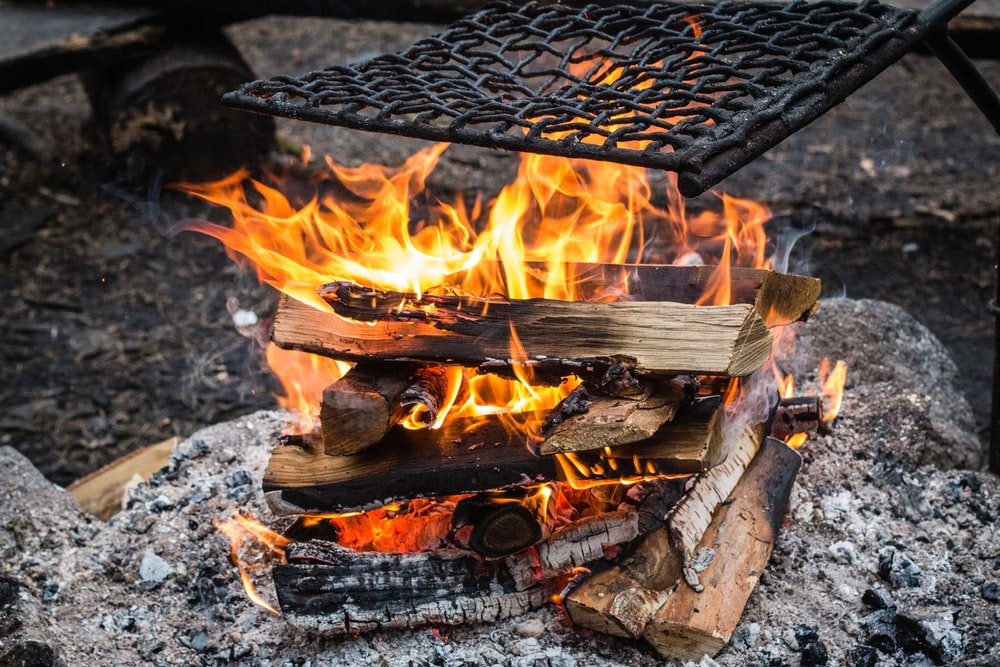closeup photography of firewood under black metal chain