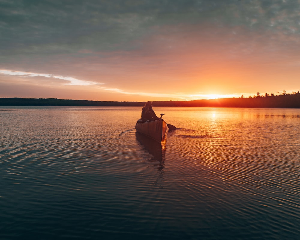 person sailing canoe during sunset