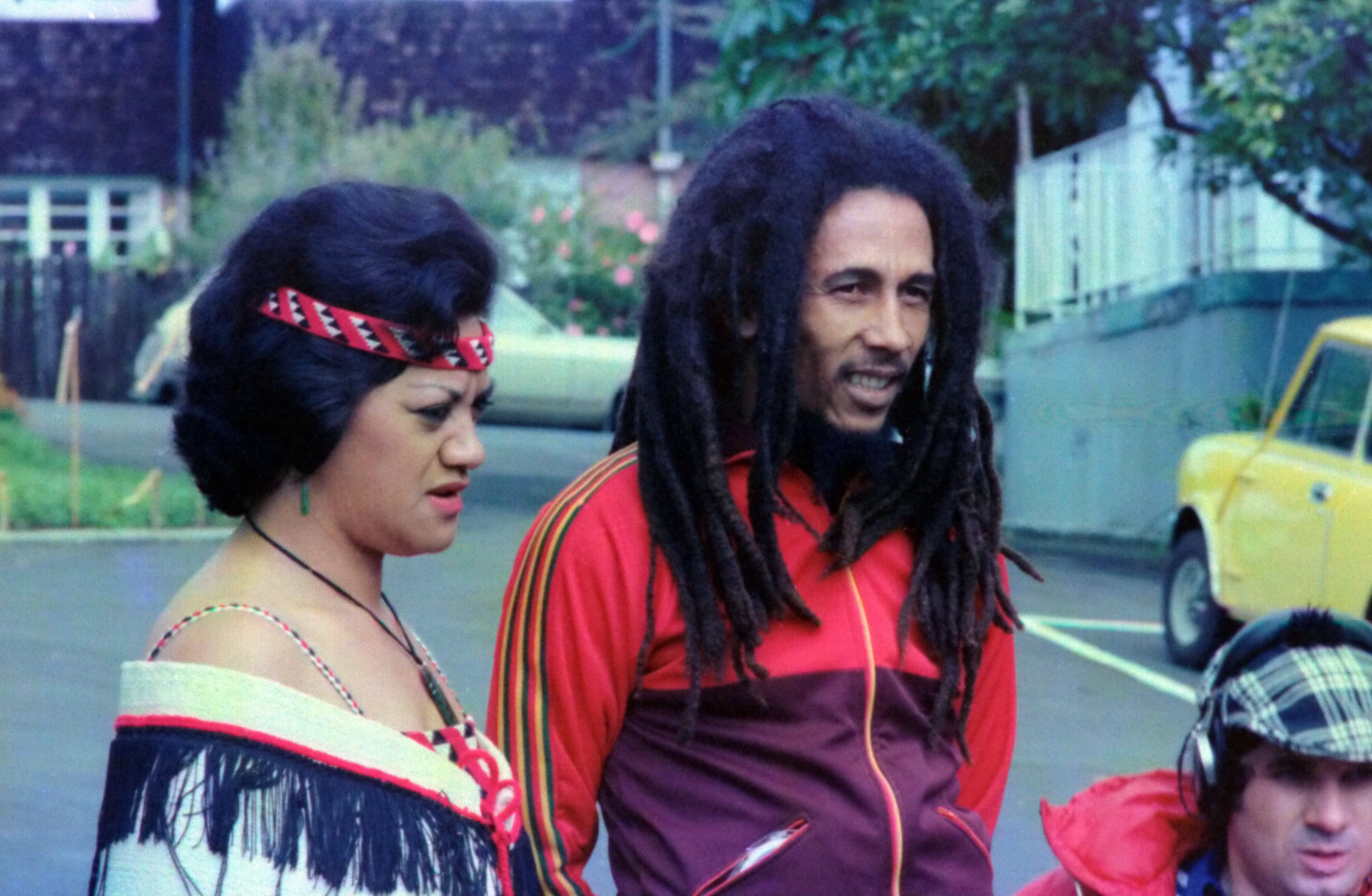 Bob Marley standing beside woman during daytime