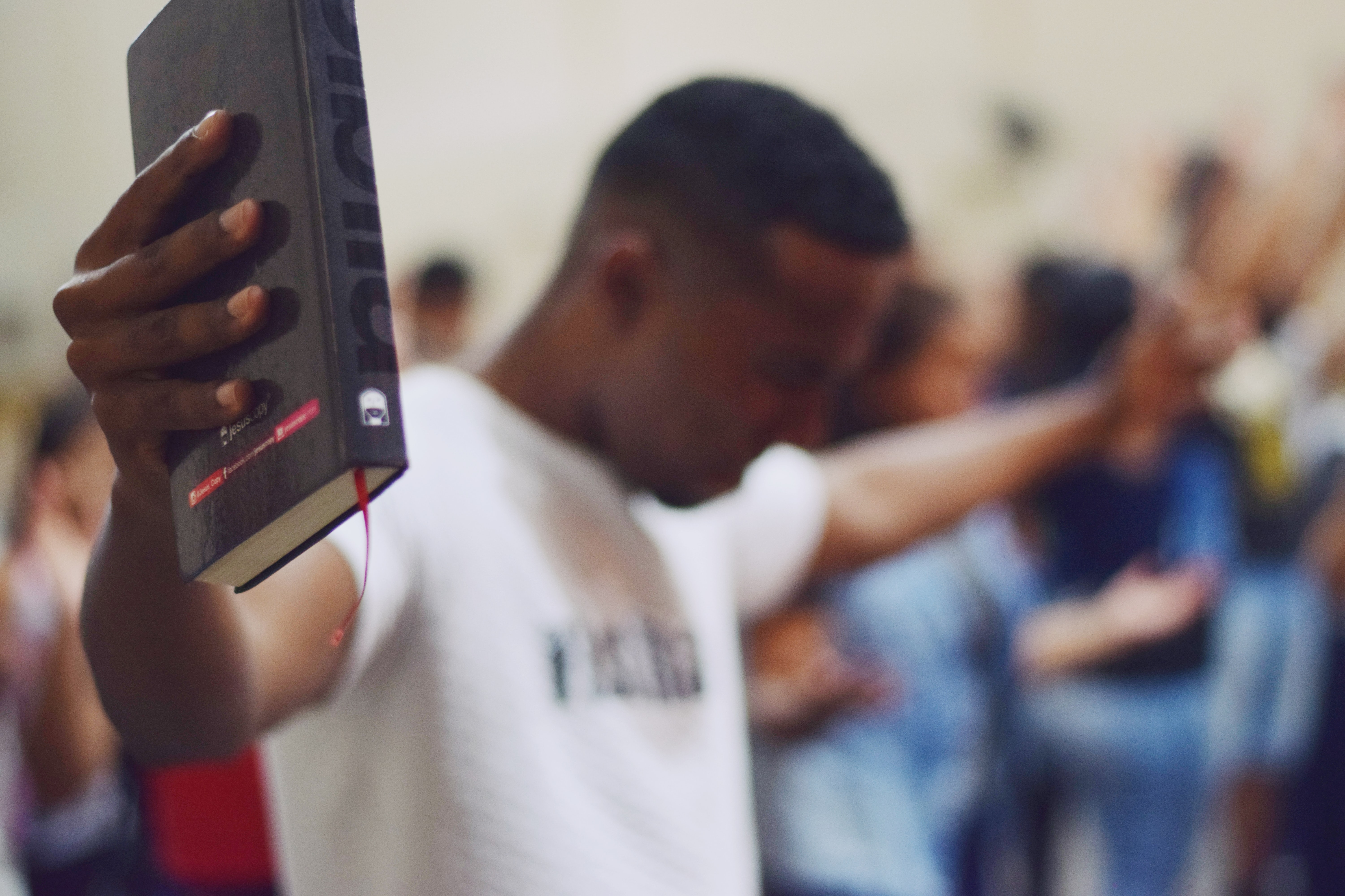 selective focus photography of man holding Holy Bible
