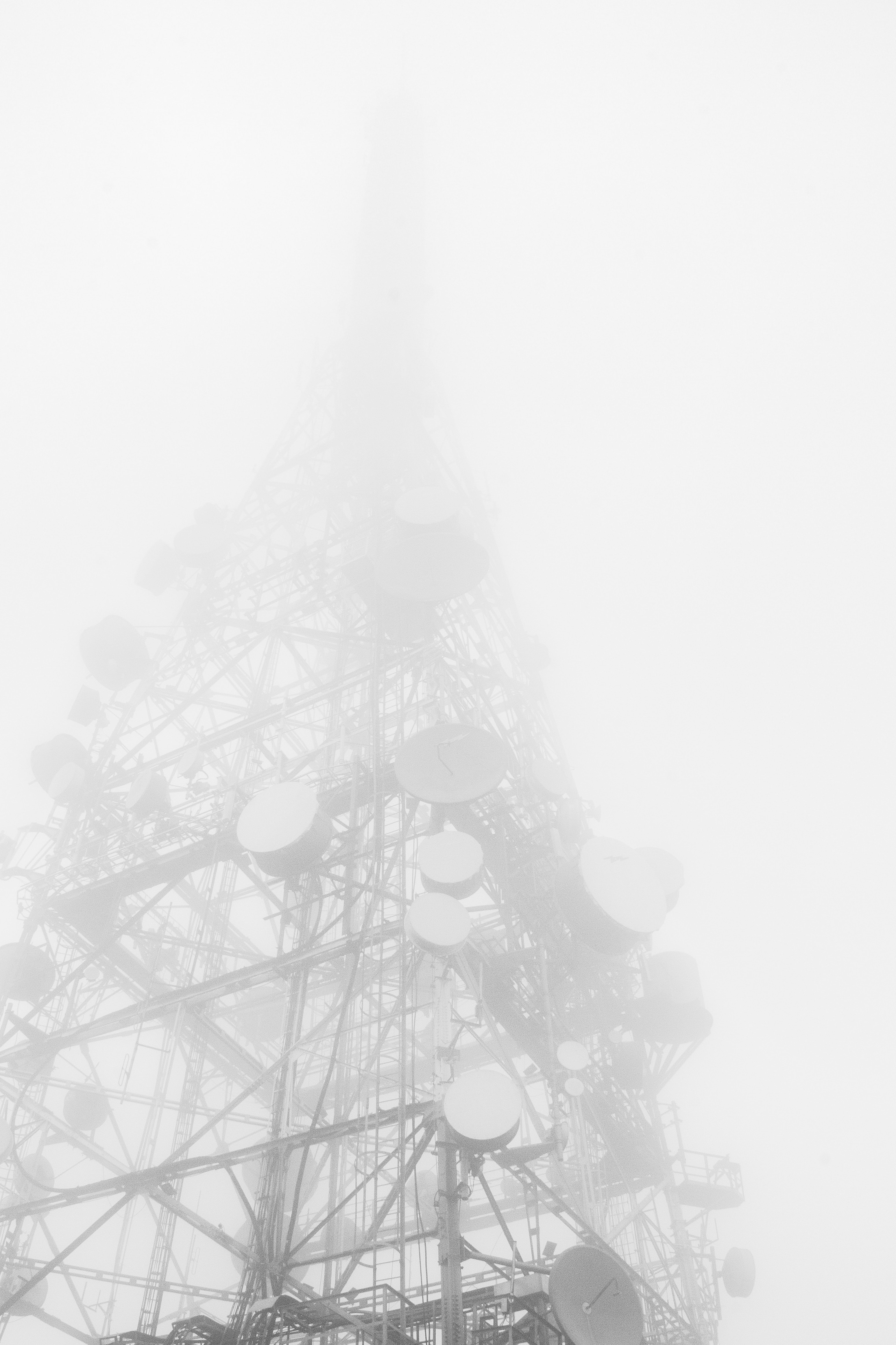 gray telecommunications tower during foggy day