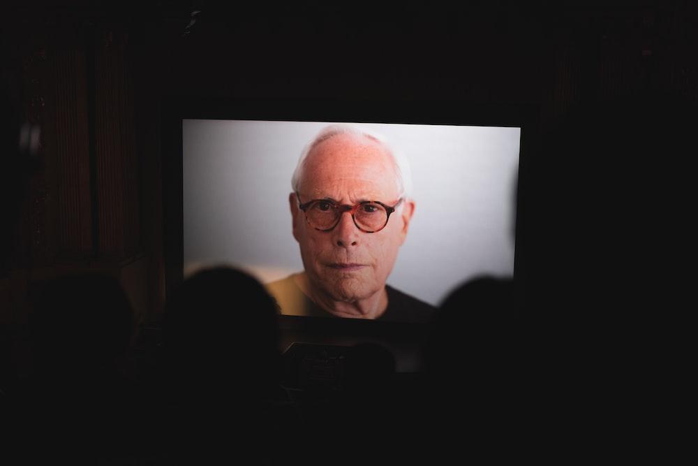 flat screen TV showing man's face