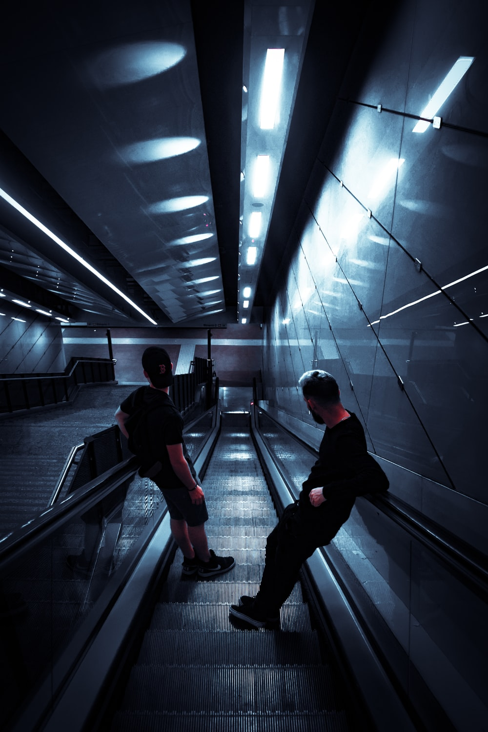 two man standing on escalator in mall