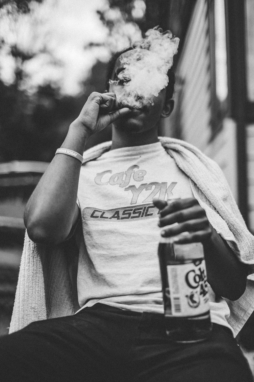 man wearing white shirt smoking