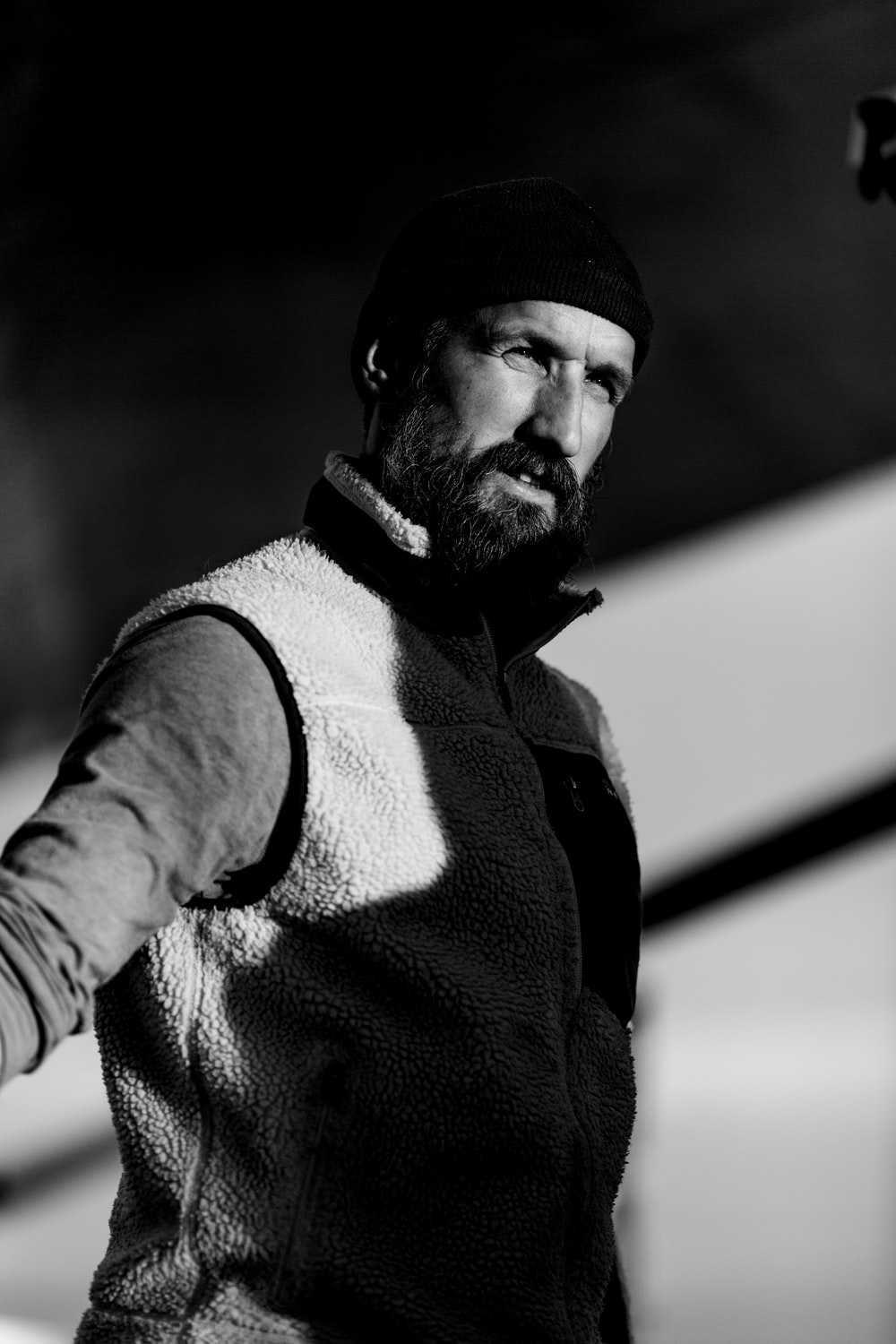 grayscale photography of man in sweater vest