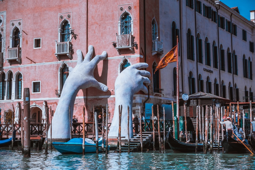 hand statue on body of water