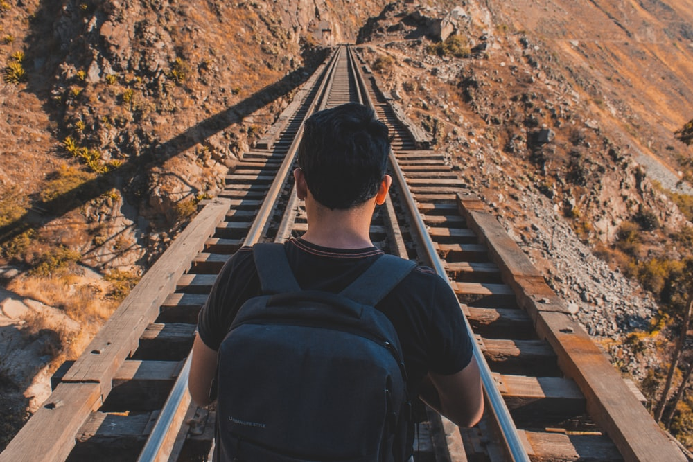 man carrying backpack while standing in the middle of railway