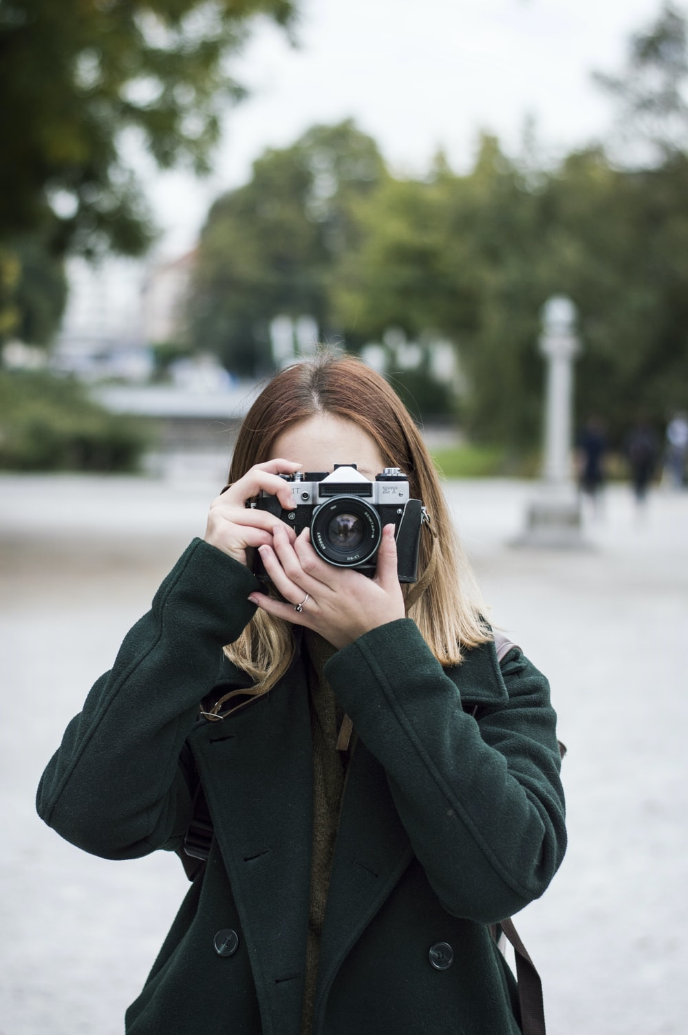 woman using SLR camera near trees during day