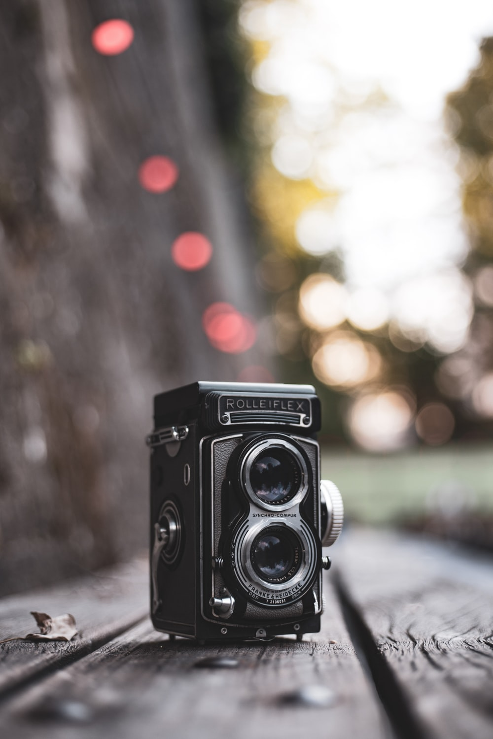 vintage black Rollerflex camera on gray wooden surface selective focus photography