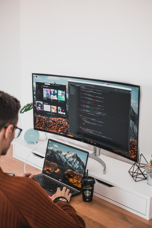 man using laptop and computer monitor