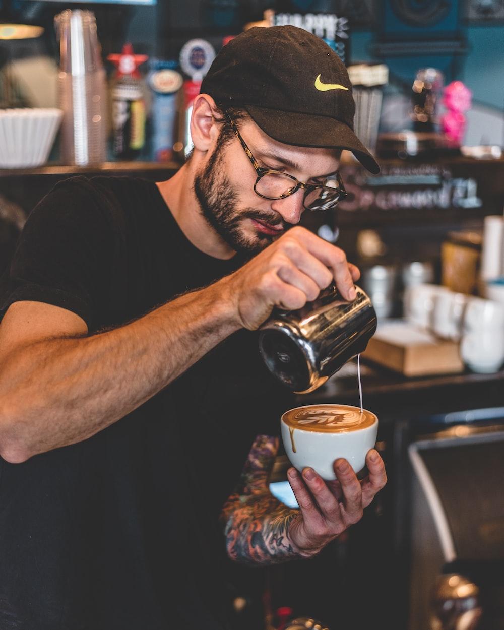 man in black shirt pouring milk on latte