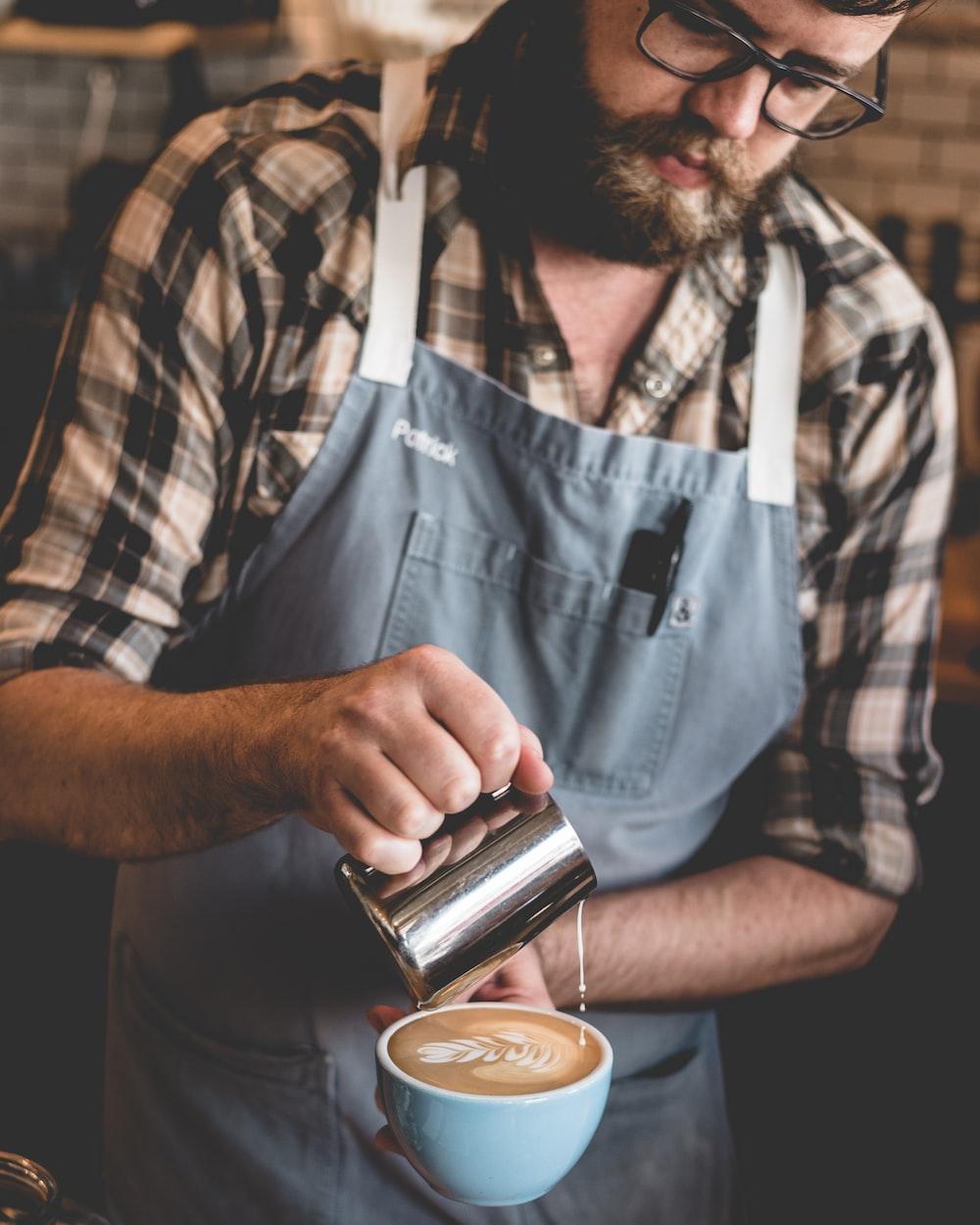 man pouring milk on latte