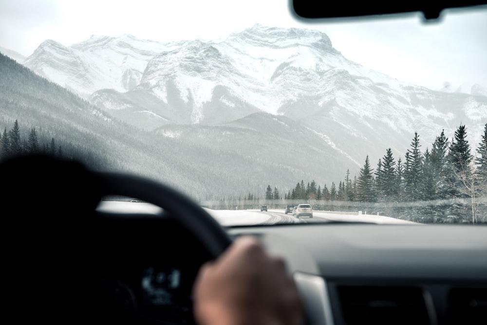 person driving facing through grey mountain