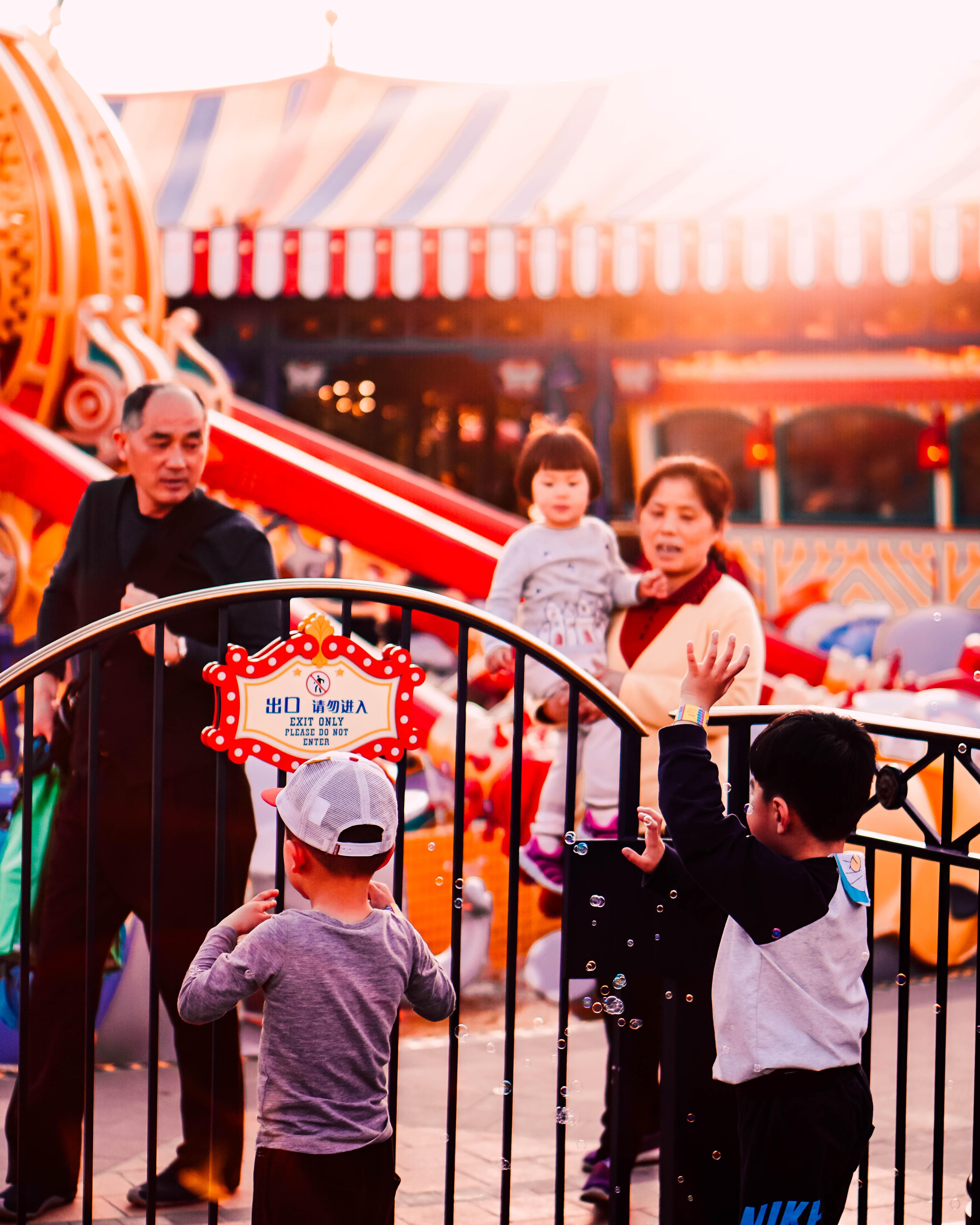 kids beside black steel gate