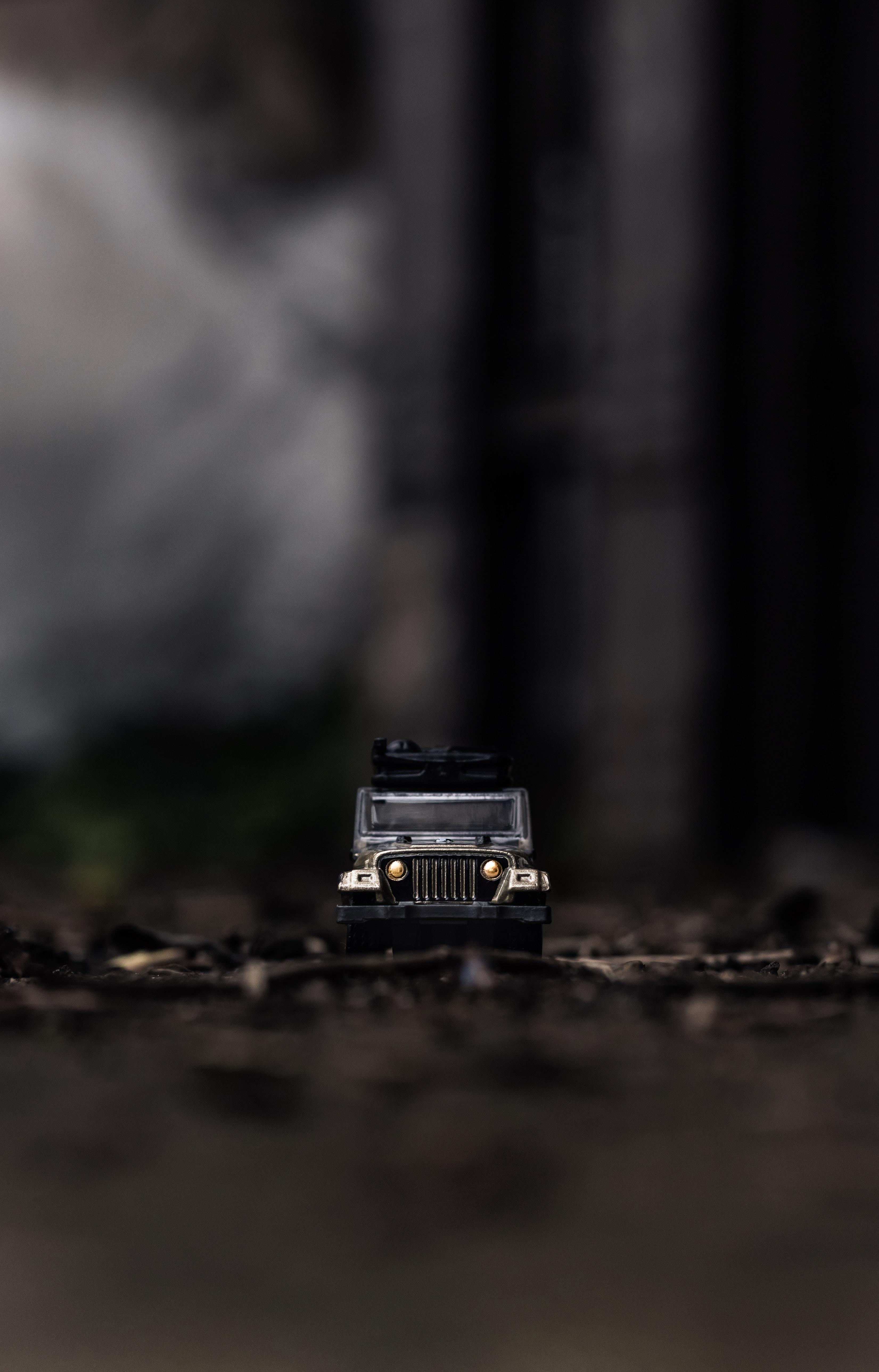 tilt shift lens photography of black Jeep toy