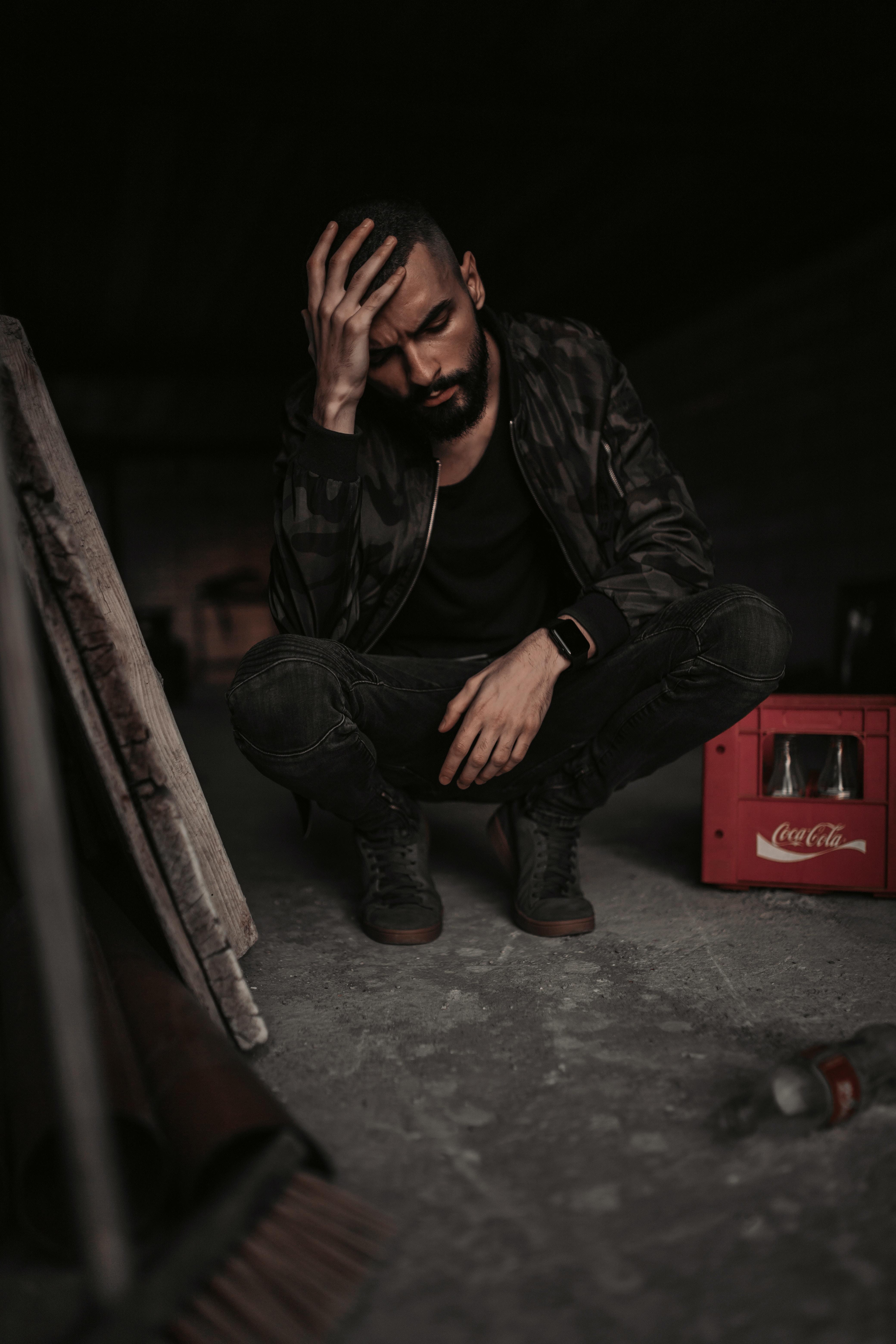 man sitting beside Coca-Cola plastic crate