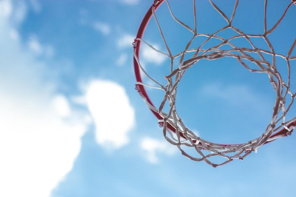 red basketball hoop under blue sky during daytime