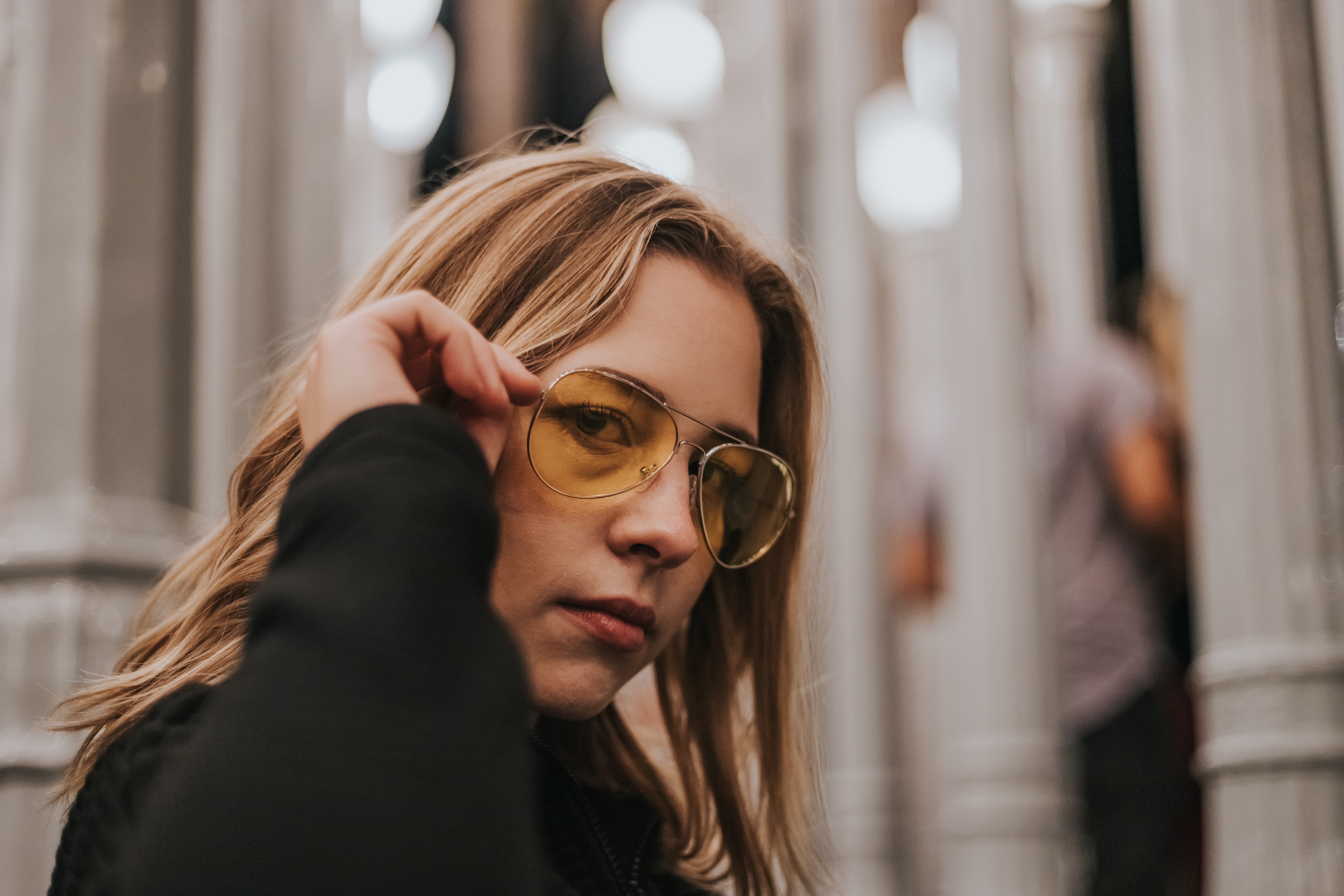 focus of photo of woman holding her sunglasses
