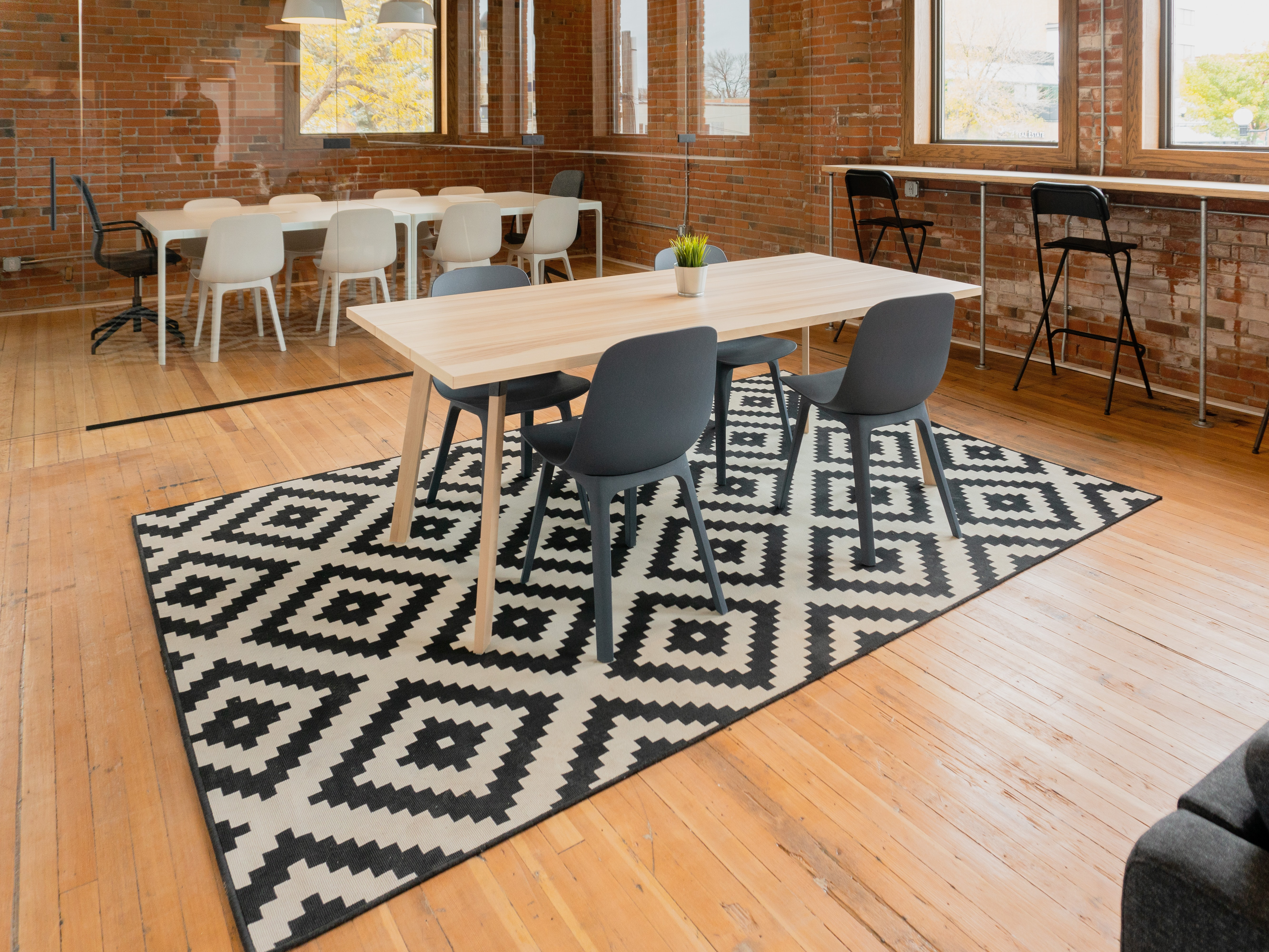 rectangular beige wooden table with four gray chairs